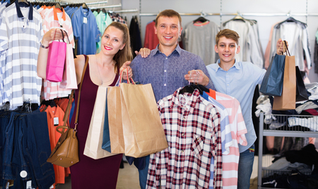 Happy positive couple and teenager with shopping bags with purchase in the store