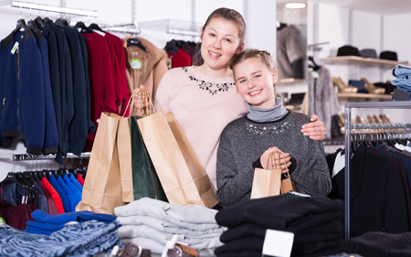 Attractive young mother and her teen daughter looking happy with shopping bags in store