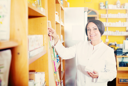Portrait of smiling mature pharmacist woman with biologically active dietary supplement package in store