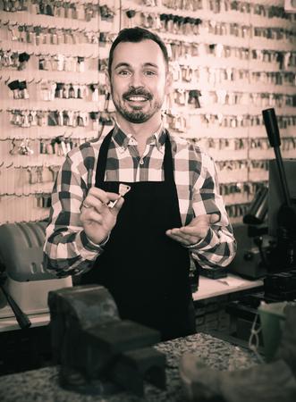 happy male worker showing key he made in repair workshop