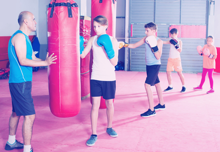 Young boys sportsmans at boxing workout on punching bag with coach