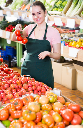 young attractive saleswoman offering ripe tomatoes behind the counter in supermarket