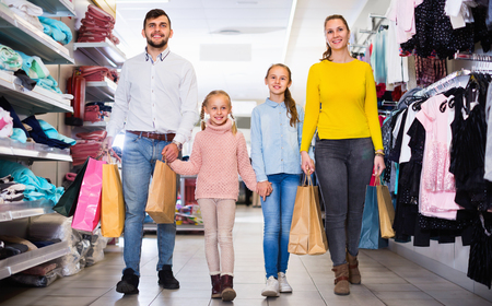 Young happy cheerful positive  parents with two little girls shopping in mall, carrying purchases