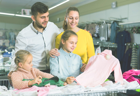 Smiling parents choosing new turtleneck for daughters in children clothing shop