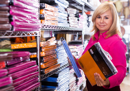 Portrait of happy mature woman looking cotton bed sheet in the store