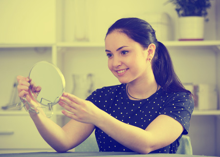 Cheerful girl sitting at table at home and looking in mirror