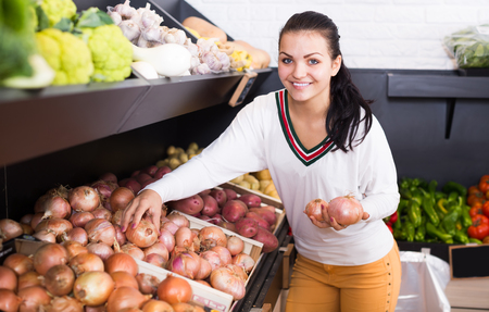 Smiling female customer examining various onions in grocery shop