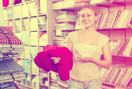 smiling young woman customer picking bright red bed cover in textile department