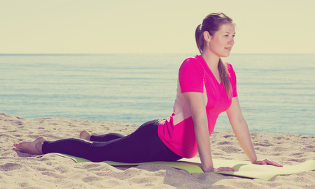 Smiling girl practicing various yoga poses during training on beach