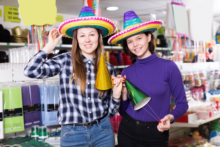 Two playfully girls in colorful party hats in festive decoration shop