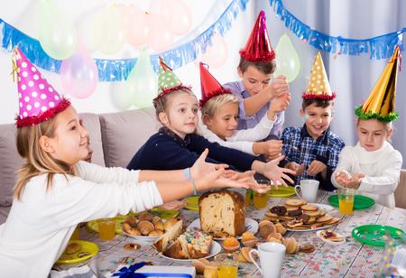Beautiful children enjoying friend's birthday during festive dinner