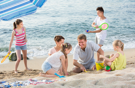 Foto de Happy family with children playing together with sand and active games on beach - Imagen libre de derechos