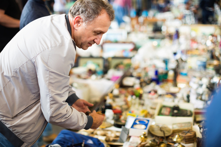 Positive glad cheerful elderly man choosing interesting souvenirs at traditional flea market