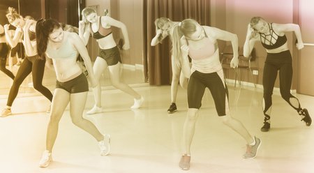 Group of young fitness girls dancing zumba in dance class