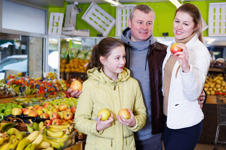 Happy family with small daughter choosing sweet ripe apples in in fruit market