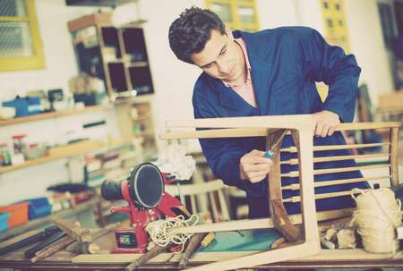 Man carpenter with screwdriver in hand working in furniture repair workshop