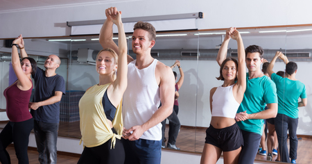 Photo for Smiling young adults dancing bachata together in dance studio - Royalty Free Image