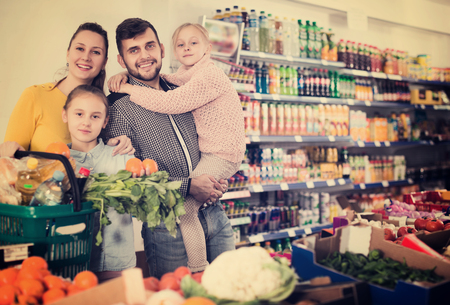 Two positive little sisters during family shopping in greengrocery department of supermarket