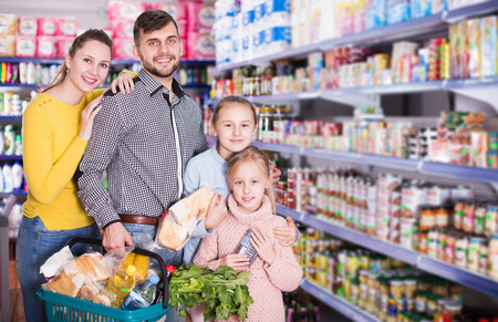 portrait of young parents with two little girls with purchases during family shopping in grocery store