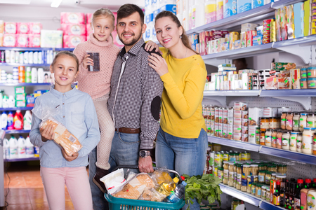 Cheerful parents with two daughters holding full basket after shopping in food store