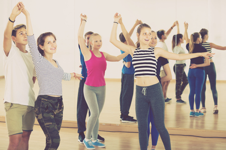 Group of energy teenagers trying dancing with partner in education classroom