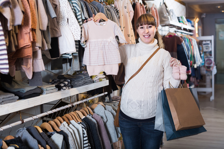 smiling english  pregnant woman showing her purchases in children's clothes shop