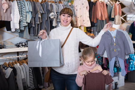 Pretty pregnant mother and girl enjoying their purchases in children's cloths shop