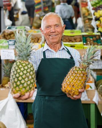 Positive senior male owner of greengrocery shop in apron offering fresh fruits and vegetables for sale