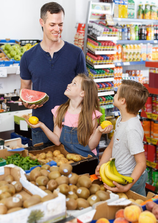 Positive man with kids looking for fresh delicious fruits in supermarket