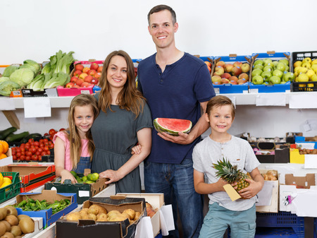marrieds with children standing near shelves with fruits  in local supermarket