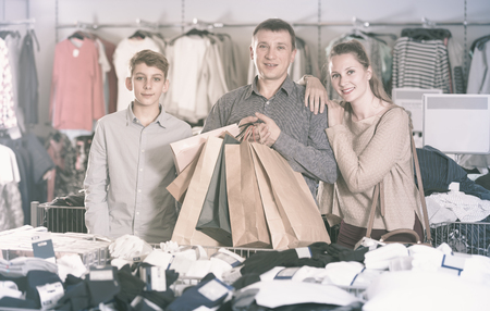 Portrait of two generations showing shopping bags with purchase in the shop
