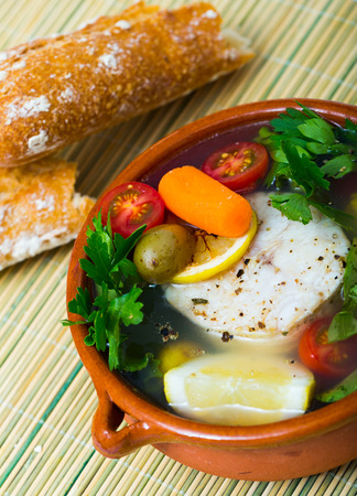 Fish soup with hake. Recipe: for broth boil hake head, add potatoes, carrot, shallots, corn and 200 gr fish fillet. Season with salt, pepper, cook in oven at 220C/428F for 40 min