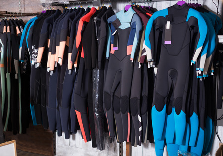 Photo pour Image of colorful wetsuit hanging in the modern european store for surfing - image libre de droit