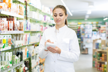 Woman pharmacist with notebook near shelves, stocktaking in drugstore