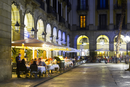 View of illuminated Placa Reial in Barcelona in warm autumn evening