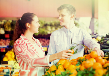 Photo pour Smiling customers buying oranges, lemons and tangerines in grocery section - image libre de droit