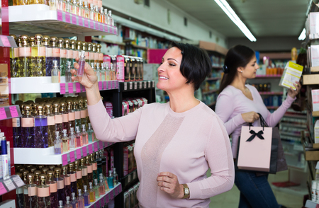 Cheerful young girl and happy mature woman choosing perfume in beauty department