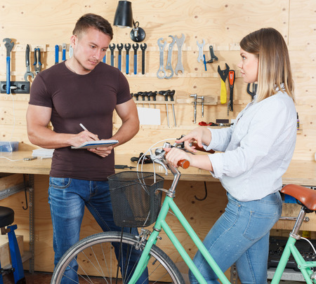 young girl consults about repairing a bicycle with a male master in the workshop.