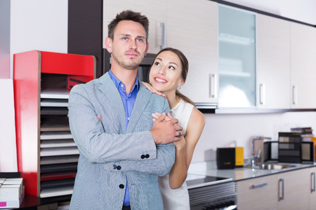 Pair of young people standing in furniture accessories store