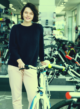 smiling female standing with bicycle in the store