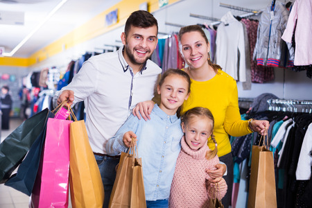 Portrait of young parents with two little girls during family shopping