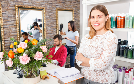 Portrait of  cheerful positive smiling woman  administrator inviting to beauty salon