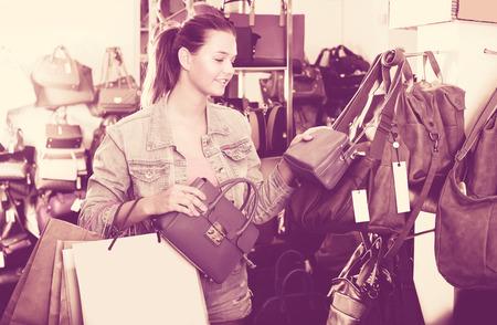 Attractive teenager girl buying handbag in fashion shop