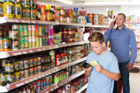 boy choosing products in food store in background with man having phone conversation