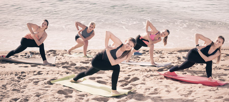 Group of women exercising yoga on sea beach on sunny day