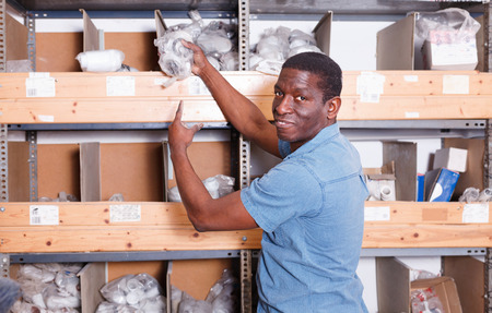 African-American glad positive man choosing materials for overhauls in building materials store