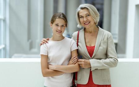 Foto de Attentive tween girl with senior woman looking with interest at gallery exposition - Imagen libre de derechos