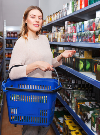 Portrait of  woman customer choosing tea in box in  grocery food store