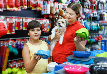 Glad cheerful positive smiling teen boy with mother visiting pet shop in search of accessories for their dog
