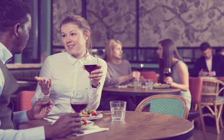 Photo pour Young woman with African American colleague on friendly meeting over dinner with wine in restaurant - image libre de droit